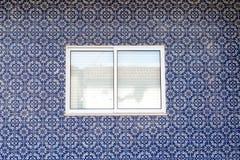在装饰的墙壁上的白色窗口有葡萄牙陶瓷砖的 免版税图库摄影