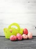 在装饰的绿色篮子的被绘的复活节彩蛋在木桌上 库存图片