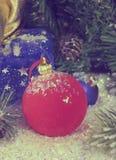 在装饰雪的红色和蓝色新年` s球和与礼物的一个袋子,定调子 库存照片