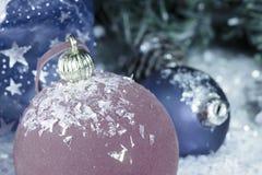 在装饰雪的红色和蓝色新年` s球和与礼物的一个袋子,定调子 免版税库存照片