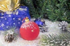 在装饰雪的红色和蓝色新年` s球和与礼物的一个袋子 库存照片