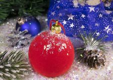 在装饰雪的红色新年` s球和与礼物的一个袋子 库存照片