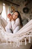 在裤子、毛线衣和温暖的拖鞋打扮的微笑的深色头发的女孩拿着坐在舒适的一个吊床的一个红色杯子 免版税库存图片