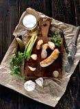 在裱糊的切板、葱、大蒜、腌汁和啤酒的烤自创香肠肉馅在黑暗的背景 免版税库存照片