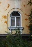 在褴褛老墙壁上的曲拱窗口 免版税库存图片
