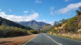 在西开普省的空的沥青路,有风景山脉和自然植被的南非 免版税库存照片