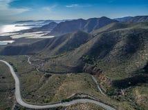 在西班牙山和一条路的鸟瞰图向有圈的海 卡塔赫钠,科斯塔布朗卡,西班牙 图库摄影