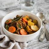 在西红柿酱和烤土豆的炖牛肉在一个白色碗 库存图片