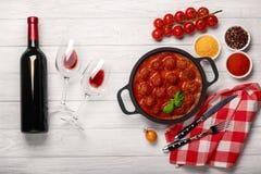 在西红柿酱的丸子在一个煎锅用樱桃、蕃茄、瓶酒和在一个白色木板的两块玻璃 库存照片