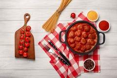在西红柿酱的丸子用在一个煎锅和西红柿的香料在一个切板和白色木板 库存图片