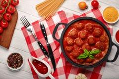 在西红柿酱的丸子用在一个煎锅和西红柿的香料在一个切板和白色木板 免版税库存照片