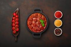 在西红柿酱的丸子用香料、西红柿、辣椒粉、姜黄和蓬蒿在一个煎锅在生锈的棕色背景 免版税库存照片