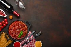 在西红柿酱的丸子用香料、西红柿、面团和蓬蒿在一个煎锅有瓶的酒和葡萄酒杯在生锈 免版税库存图片