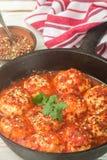 在西红柿酱的丸子用香料和大蒜在一个黑塑象 库存照片