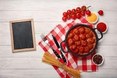 在西红柿酱的丸子用香料,在一个煎锅的西红柿在一个白色木板 免版税图库摄影