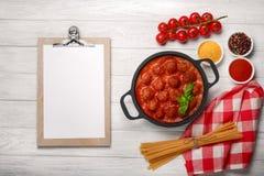 在西红柿酱的在一个煎锅和西红柿的丸子用香料和蓬蒿在一个白色木板 图库摄影