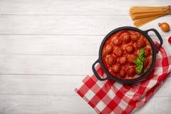 在西红柿酱的在一个煎锅的丸子用香料和蓬蒿在一个白色木板 库存照片