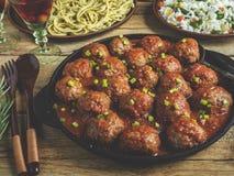 在西红柿酱的自创丸子 木表面上的煎锅,与菜的米,面团 免版税库存图片