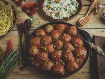 在西红柿酱的自创丸子 木表面上的煎锅,与菜的米,面团 免版税库存照片