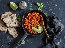在西红柿酱的被炖的豆在生铁平底锅和家制面包 库存图片
