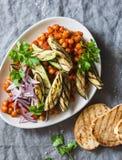 在西红柿酱的被炖的鸡豆、烤茄子和夏南瓜、烤面包-一道可口开胃菜或快餐 库存图片