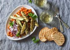 在西红柿酱的被炖的鸡豆、烤茄子和夏南瓜、白葡萄酒、烤面包-一道可口开胃菜或快餐 Vege 免版税库存图片