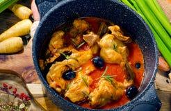 在西红柿酱的被烘烤的兔子用黑橄榄和新鲜的草本 图库摄影