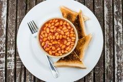 在西红柿酱的被烘烤的豆用干的烤面包 免版税库存照片