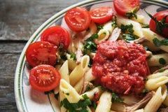在西红柿酱的Penne面团与鸡,蕃茄装饰了荷兰芹 免版税图库摄影