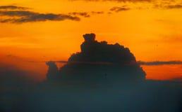 在西部的橙色天空与一朵大云彩的阴影 图库摄影