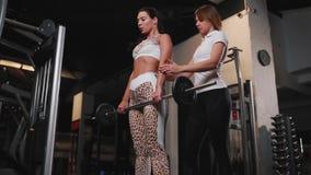 在要做有长的黑发的锻炼deadlift女性女性客户的白色T恤杉帮助的个人女性教练员 股票视频