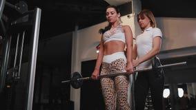 在要做有长的黑发的锻炼deadlift女性女性客户的白色T恤杉帮助的个人女性教练员 影视素材