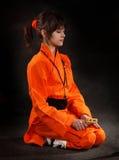 在要思考的橙色服装的女孩wushu 库存照片