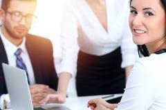 在见面的商人队在办公室 在指向入膝上型计算机的女商人的焦点 配合或教练概念 库存照片