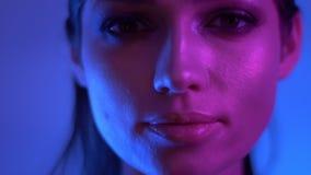 在观看与神奇微笑的五颜六色的紫色和蓝色霓虹灯的未来派时装模特儿入照相机在演播室 股票录像