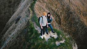 在观看史诗日落海景的愉快的年轻新婚佳偶夫妇附近的寄生虫飞行亲吻在诺曼底海岸峭壁顶部 股票录像