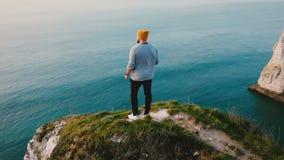 在观看史诗海景的年轻成功的旅游人附近的寄生虫飞行在诺曼底日落海岸峭壁岩石顶部 影视素材
