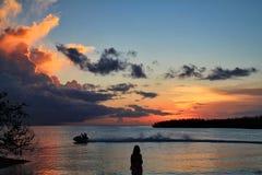 在观看在天际的jetski的摄影师剪影和夫妇深刻的橙色日落在阔边帽在马拉松钥匙靠岸 免版税库存图片
