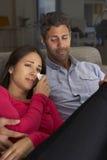 在观看在电视的沙发的西班牙夫妇哀伤的电影 免版税库存图片