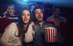 在观看恐怖片的戏院的年轻夫妇 免版税库存图片