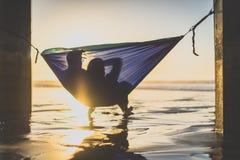 在观看日落的吊床的夫妇 库存图片