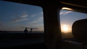 在观看日落的爱的夫妇在海通过汽车的旁边和后窗 库存照片