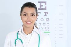 在视力检查表附近的女孩的医生 免版税库存图片