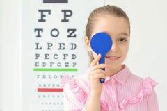 在视力检查表附近的逗人喜爱的小女孩在办公室 免版税库存图片
