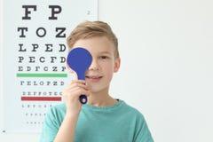 在视力检查表附近的逗人喜爱的小男孩在办公室 图库摄影