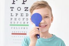 在视力检查表附近的逗人喜爱的小男孩在办公室 库存照片