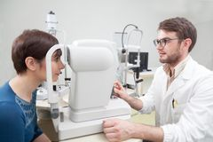 在视力测验期间的少妇与眼科医生 图库摄影