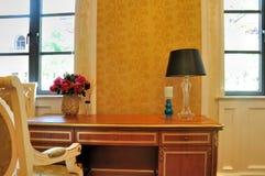 在视窗之下的明亮的书桌 免版税库存照片