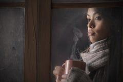 在视窗之后的美丽的妇女与一杯咖啡 免版税图库摄影