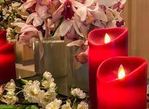 在角落的红色人为蜡烛与小组作为葡萄酒使用的品种花在豪华卧室称呼装饰 免版税库存照片